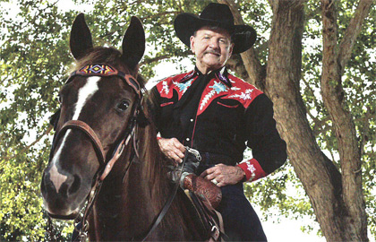 Ron Bergeron styling a black cowboy hat riding on a short haired brown horse