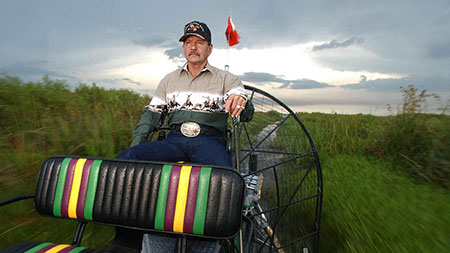 A man wearing a hat on a airboat in the everglades