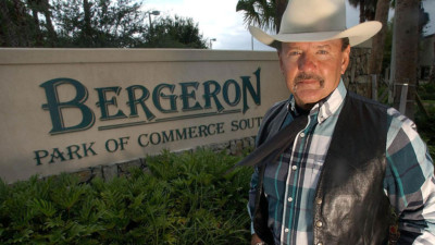 Ron Bergeron standing with a cowboy hat on in front of the entrance sign Bergeron Park Of Commerce South